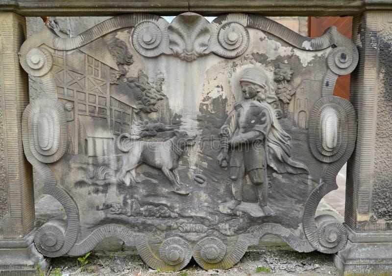 Bas-relevo antigo o menino e um cão em Gdansk, Polônia imagem de stock royalty free