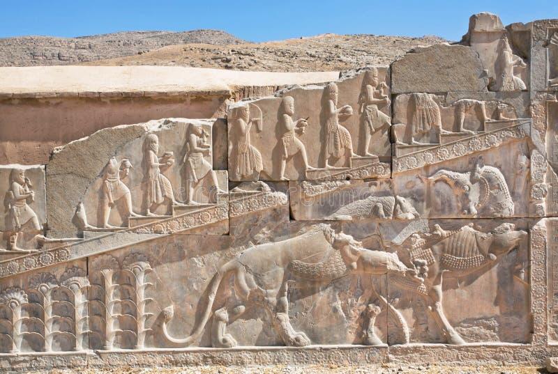 Bas-relevo com símbolos dos Zoroastrians - touro de combate e um leão, Persepolis fotografia de stock