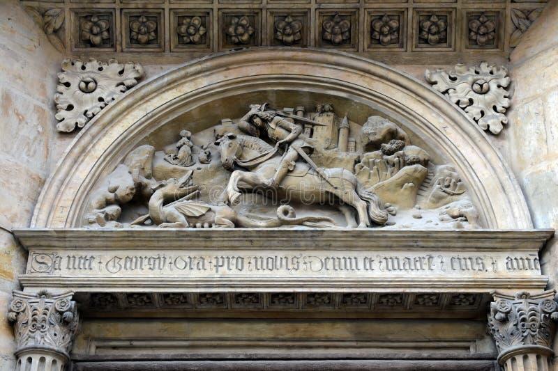 Bas-relevo que descreve St George que luta o dragão no portal do sul da basílica com o castelo de Praga da rua de Yeresko imagens de stock