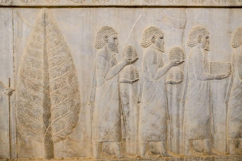 A bas-relief of ancient Greeks at Apadana, Persepolis. Shiraz, Iran. A bas-relief of ancient Greeks men were bearing gifts at Apadana, East Stairs, southern royalty free stock images