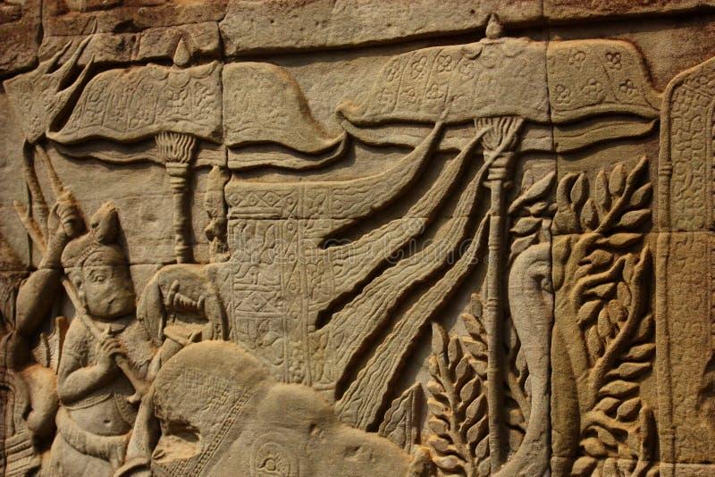Bas Relief historique dépeignant les guerriers antiques de Khmer dans la formation et faisant la bataille, Siem Reap photo libre de droits