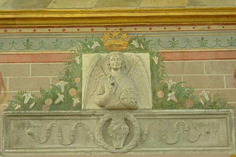 Bas relief of winged angel holding a cross, detail of the chapel of the abbey of Chaalis royalty free stock images