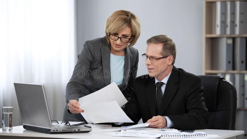 Basa att se till och med den finansiella rapporten för utkastet som göras av hans kvinnliga revisor royaltyfria bilder