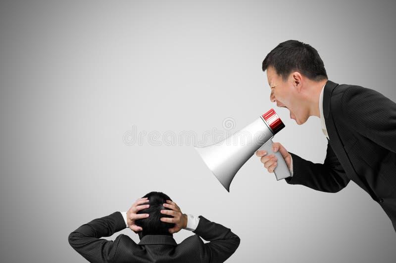 Basa genom att använda megafonen som skriker på hans anställd med betongväggen royaltyfria foton
