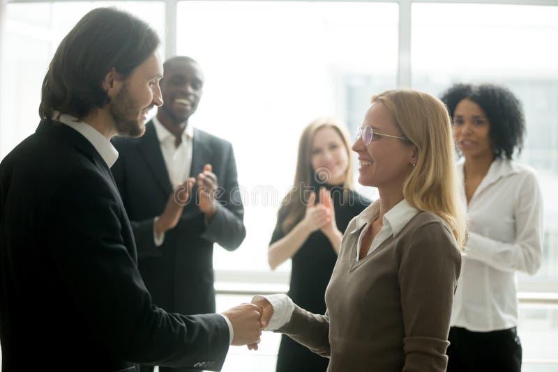Basa handshakinganställd som gratulerar med befordran medan di arkivfoton
