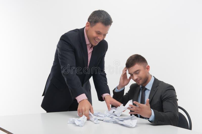 Basa ilsket med ungt anställdsammanträde på skrivbordet fotografering för bildbyråer