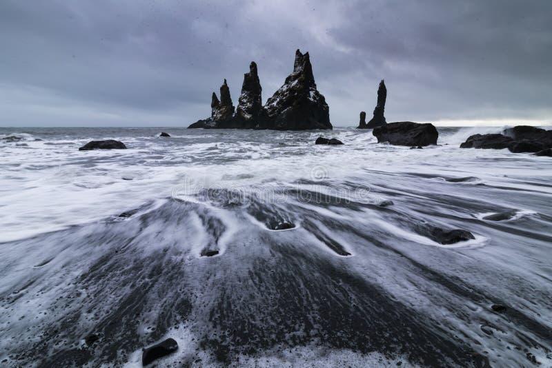 Basalt rocks Troll toes on black beach. at storm Reynisdrangar, Vik, Iceland. Basalt rock formations Troll toes on black beach. at storm Reynisdrangar, Vik royalty free stock images