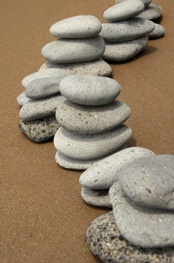 Basaltstenar på strand arkivbild