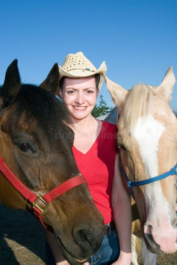 Basamenti che sorridono con i cavalli - verticale della donna immagine stock libera da diritti