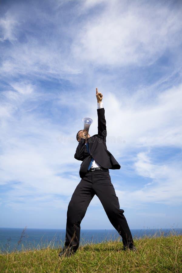 Basamento dell'uomo d'affari sulla collina e sul megafono della holding fotografia stock libera da diritti
