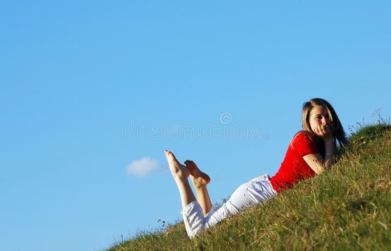 Basamento della donna nel campo di erba fotografie stock