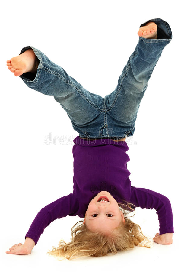 Basamento della mano del bambino della ragazza che si leva in piedi sulla testa immagini stock