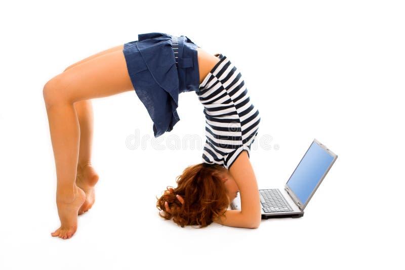 Basamento della ragazza di bellezza sulla testa con il computer portatile immagine stock