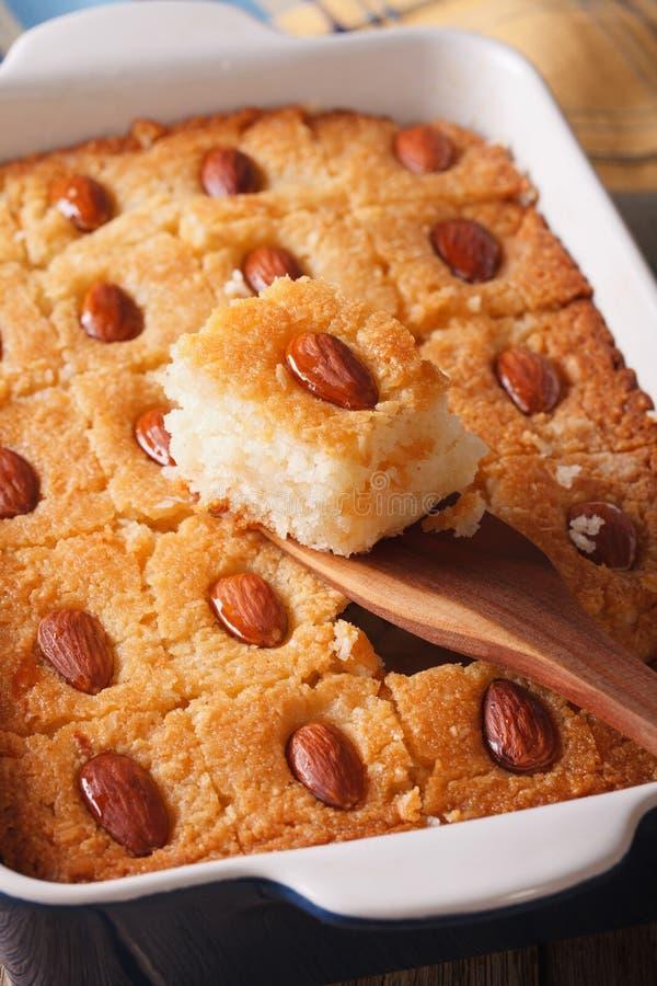 Basbousa-Torte mit den Mandeln Makro in einer Backform vertikal lizenzfreies stockfoto