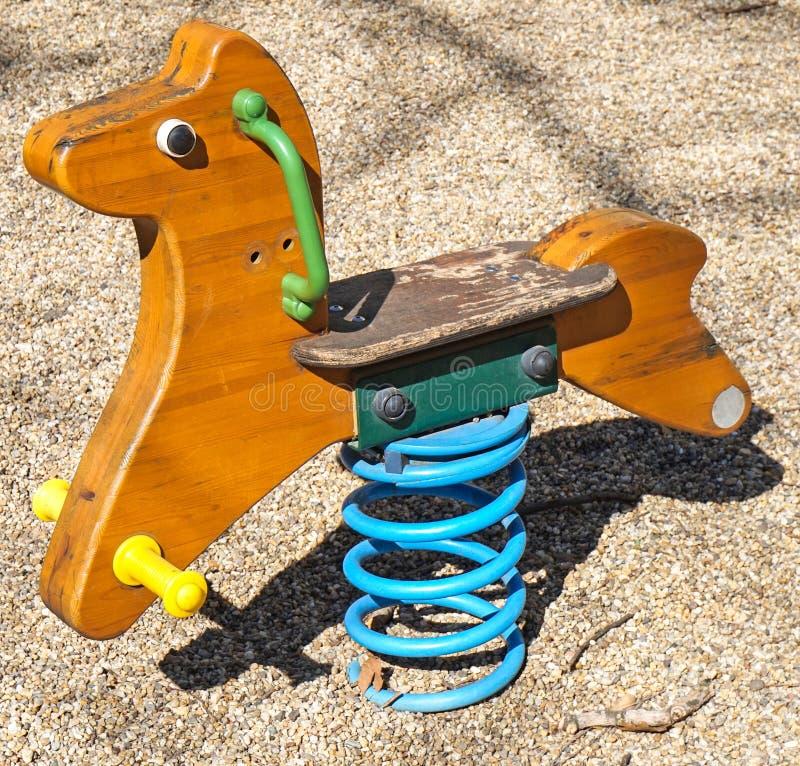 Bascula a forma di cavallo al campo da giuoco immagine stock