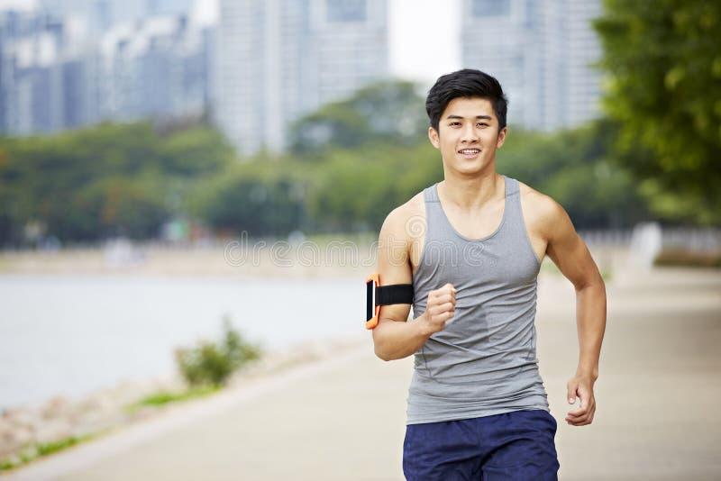 Basculador asiático joven que corre en parque imagen de archivo