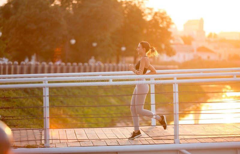 Basculador desportivo alegre que corre na ponte na manhã foto de stock royalty free