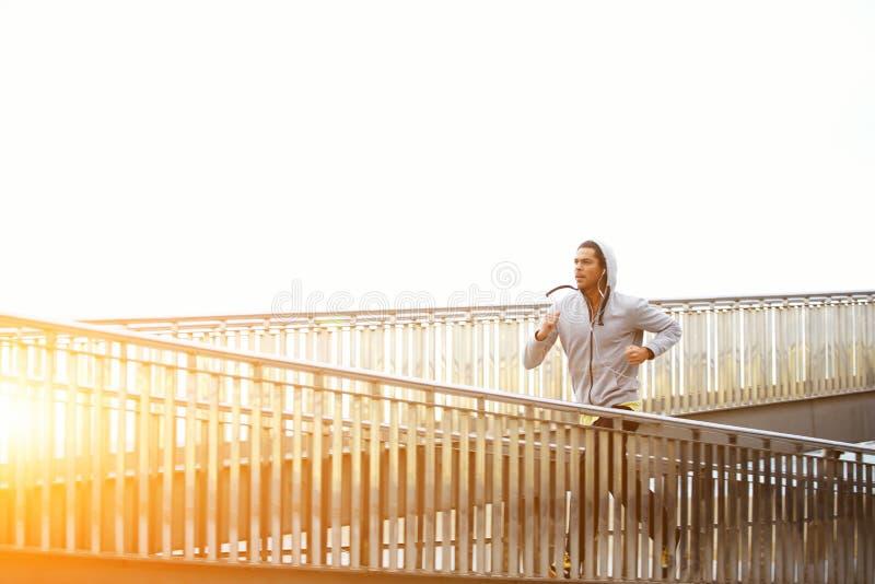 Basculador masculino que ejercita mientras que escucha la música con los auriculares fotos de archivo