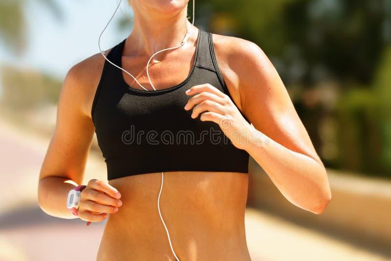 Basculador que corre en Sportsbra con los auriculares de la música imágenes de archivo libres de regalías