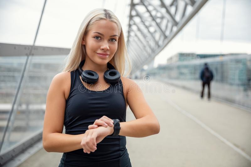 Basculador urbano femenino que comprueba al perseguidor de Smartwatch en el puente foto de archivo