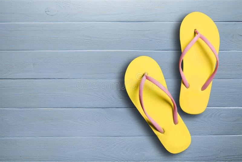 Bascules électroniques en caoutchouc jaunes de sandales sur en bois photos libres de droits