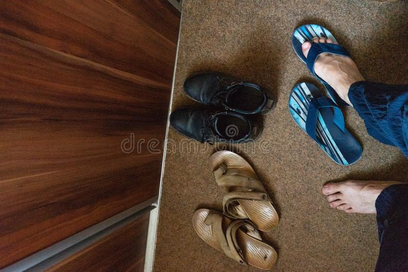 Bascules électroniques et pieds bleus dans une entrée de la maison chaussures noires et tapis démodé brun Porte en bois pour la g image stock