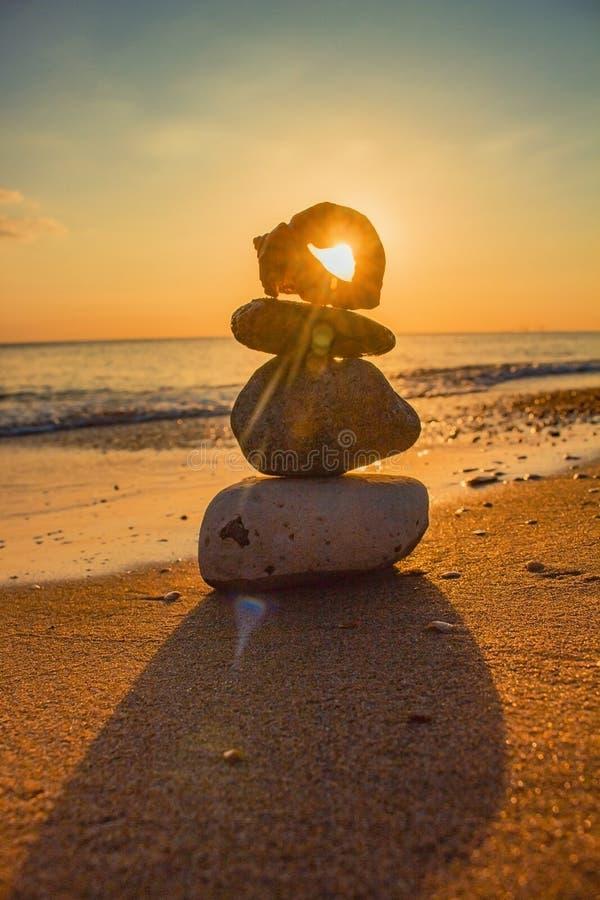 Basculez la pyramide de zen des pierres jaunes sur un fond de ciel bleu et de mer Concept de l'équilibre, de l'harmonie et de la  photo libre de droits