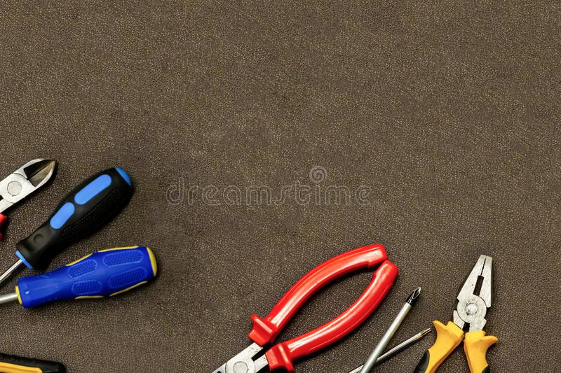 Base angle frame industrial design base screwdriver nippers red yellow pliers set of tools on a brown background stock photo