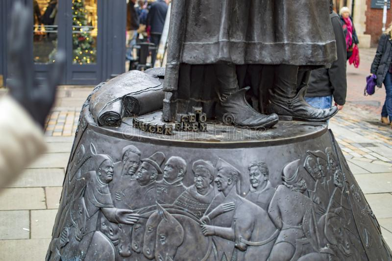 The base of bronze statue of Geoffrey Chaucer in kent canterbury town. With faces painted royalty free stock photography