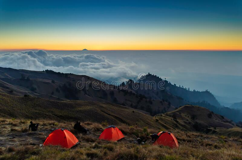 Base Camp at Mt. Rinjani volcano at Lombok island, Indonesia at sunset, far away is Mt. Agung volcano at Bali island royalty free stock images