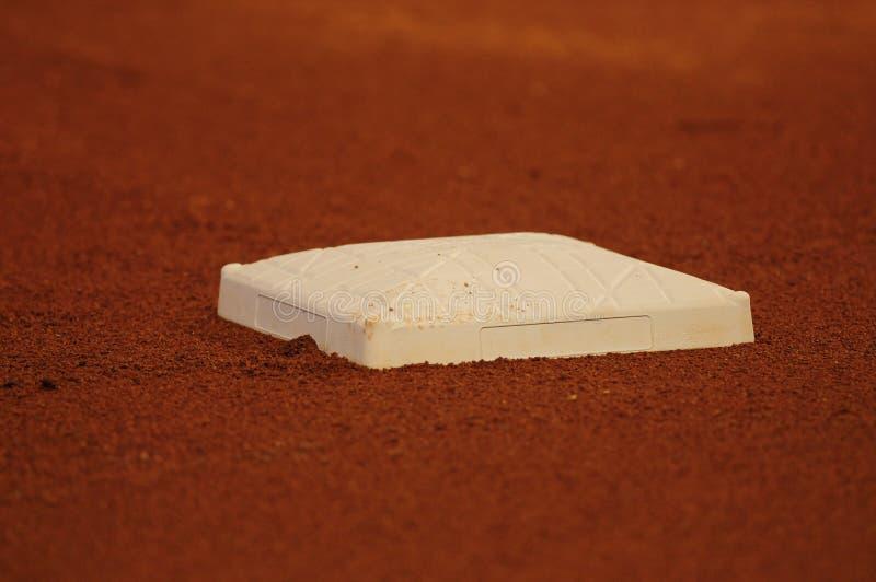 Base de base-ball sur la saleté sur la zone images stock