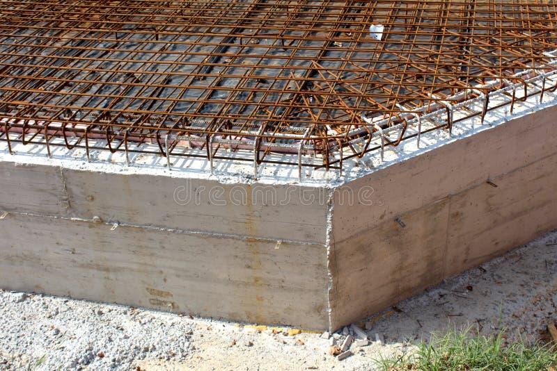 Base de construction concrète avec le filet rouillé en masse étendu de construction en métal sur l'isolation à la construction de photographie stock