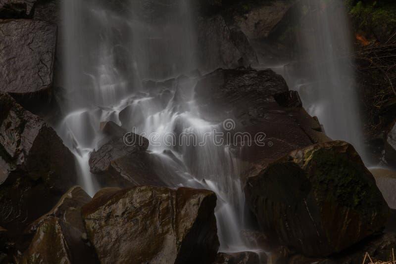 Base de la cascada, agua que conecta en cascada en rocas fotos de archivo libres de regalías