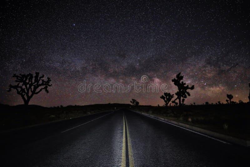 Base de la vía láctea con el camino en el desierto de Joshua Tree National Park imágenes de archivo libres de regalías