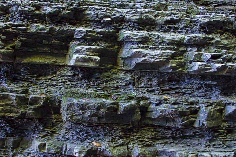 Base en pierre couverte humide in?gale de conception de fond en gros plan dur ext?rieur gris-fonc? de cascade de mur de mousse de photographie stock