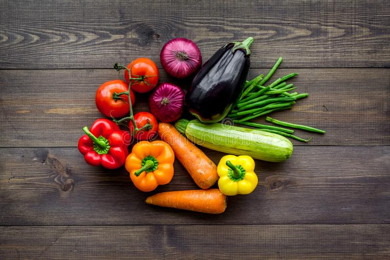 Base of healthy diet. Vegetables paprika, tomatoes, carrot, zucchini, eggplant on dark wooden background top view stock photo