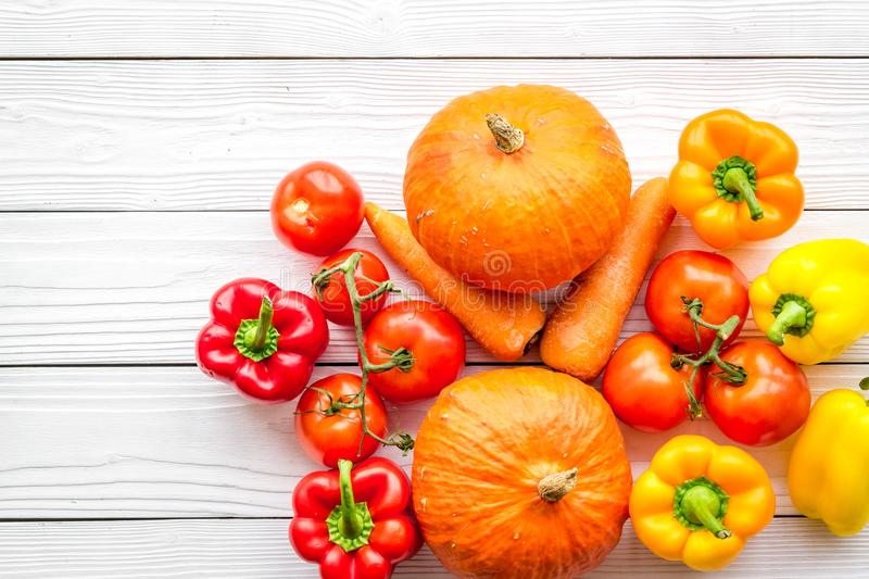 Base of healthy diet. Vegetables pumpkin, paprika, tomatoes, carrot on white wooden background top view stock images
