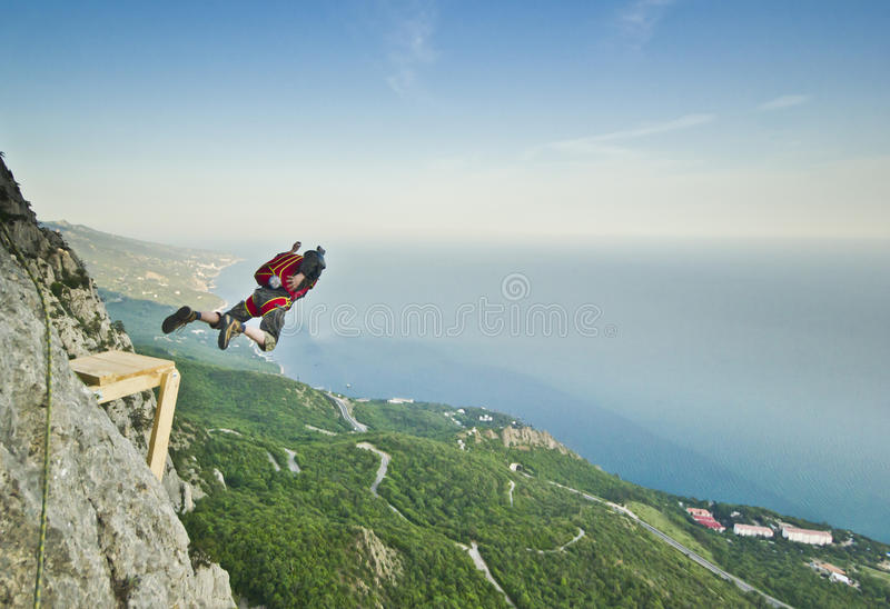 Base-jumper jumps from the cliff. Base-jumper prepears to jump from the cliff at sunrise in the mountains royalty free stock image