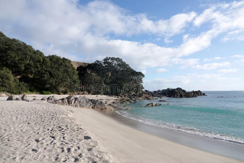 Mount Maunganui beach in Tauranga, New Zealand. From the base of Mount Maunganui, a white sand surf beach stretches as far as the eye can see on a peninsula at stock photography