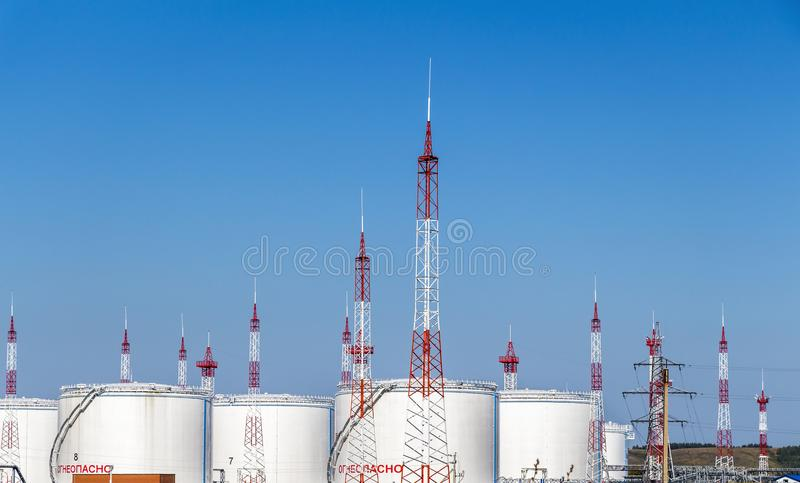 Base of oil storage. White large oil storage tanks against the blue sky royalty free stock image