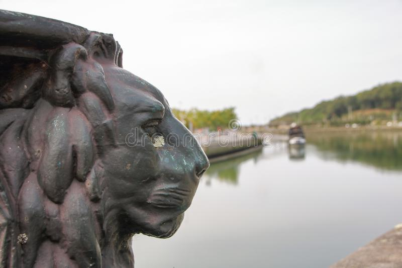 Base of a street lamp in form of a lion. On a bridge at Bayonne, Aquitaine, France stock images