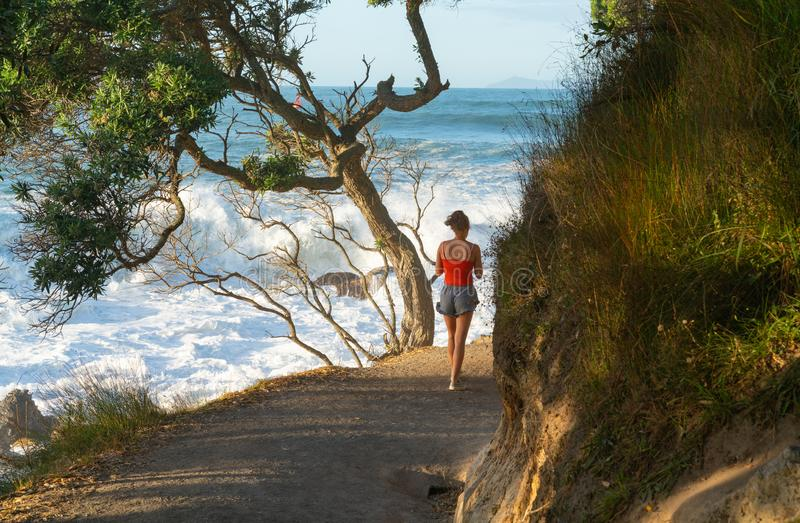 Base track popular walk with people walking caught in suns raysoff sea. MOUNT MAUNGANUI NEW ZEALAND - FEBRUARY 10 2019: Base track popular walk with people royalty free stock photos