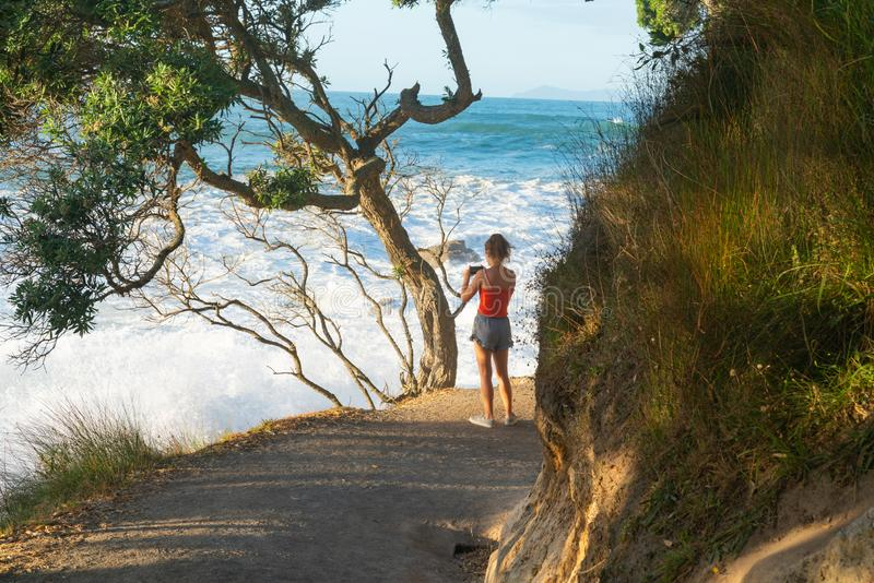 Base track popular walk with people walking caught in suns raysoff sea. MOUNT MAUNGANUI NEW ZEALAND - FEBRUARY 10 2019: Base track popular walk with people royalty free stock photo