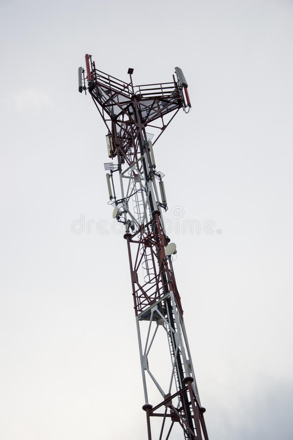 Base transceiver station (BTS) with antenna isolated on blue sky background. Telecommunications radio tower cells.  stock photos