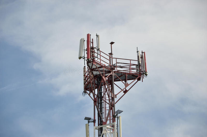 Base transceiver station (BTS) with antenna isolated on blue sky background. Telecommunications radio tower cells.  royalty free stock image