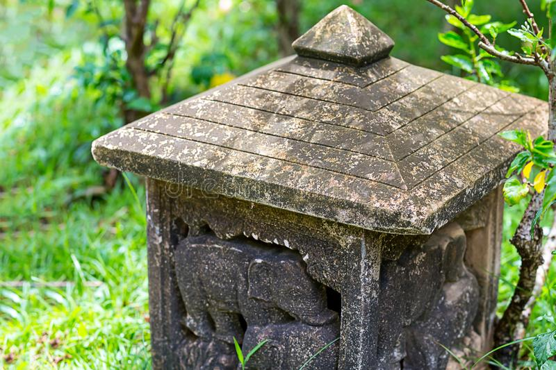 Base vintage stone old lamp in the garden of the tradition of Asia carved figures of animal elephants with a triangular roof stock photos