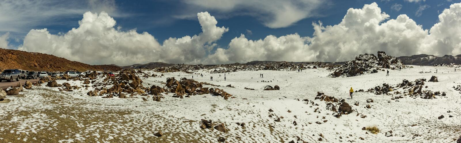 Base of volcano Teide. Valley of lava with white snow spots, partly covered by the beautiful clouds. Bright blue sky. Teide stock images