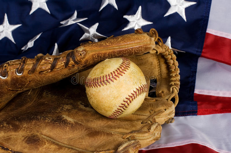 Baseball and American Flag. Old baseball in glove resting on American Flag royalty free stock photos