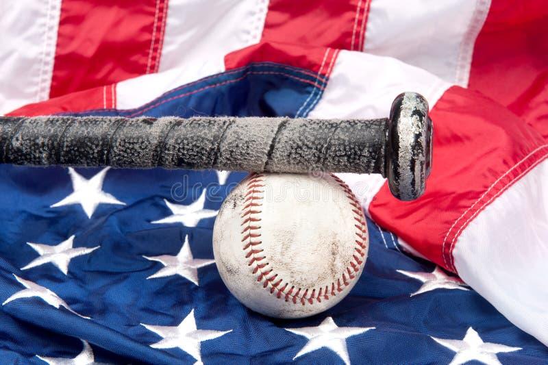 Baseball on American flag. Baseball equipment including a bat and a baseball on an American flag royalty free stock photos