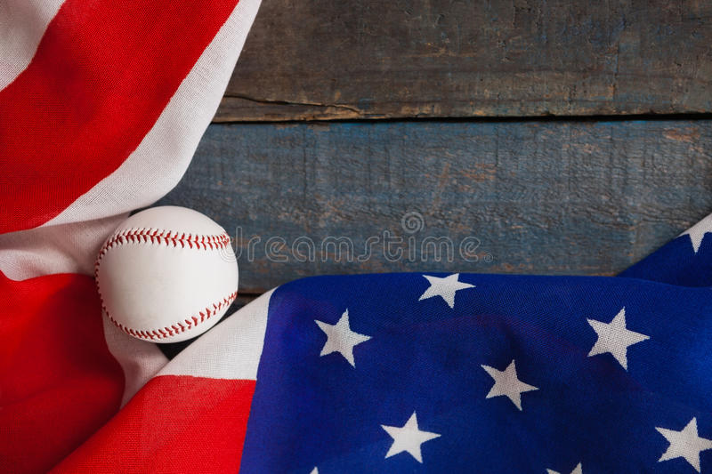 Baseball and American flag on wooden table. Overhead view of baseball and American flag on wooden table stock photography